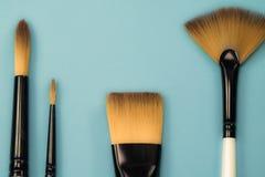 La gamma artistica di concetto di fan piano dei pennelli rotondo con i capelli naturali del nero rizza sul fondo blu del turchese Fotografia Stock Libera da Diritti