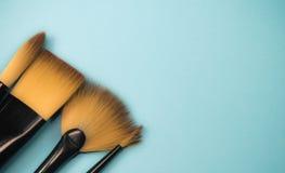 La gamma artistica di concetto di fan piano dei pennelli rotondo con i capelli naturali del nero rizza sul fondo blu del turchese Fotografia Stock