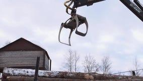 La garra de la grúa del cargador del camión coge árboles cutted madera de construcción almacen de metraje de vídeo