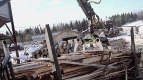 La garra de la grúa del cargador del camión coge la basura de los tablones de la serrería metrajes