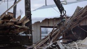 La garra de la grúa del cargador del camión coge la basura de madera de la madera de construcción metrajes