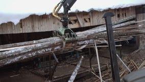 La garra de la grúa del cargador del camión levanta para arriba la basura de madera de la serrería almacen de metraje de vídeo