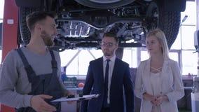 La gasolinera, el amo masculino que habla con un par joven cerca del automóvil aumentado en la elevación hidráulica da llaves y s almacen de video