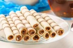 La gaufrette rayée roule, casse-croûte délicieux de chocolat sur la table en bois blanche Photo stock