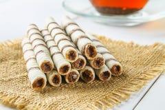 La gaufrette rayée roule, casse-croûte délicieux de chocolat sur la table en bois blanche Image stock
