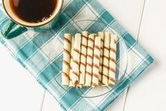 La gaufrette rayée roule, casse-croûte délicieux de chocolat sur la table en bois blanche Images libres de droits