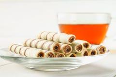 La gaufrette rayée roule, casse-croûte délicieux de chocolat sur la table en bois blanche Photo libre de droits