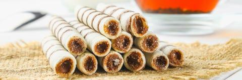 La gaufrette rayée roule, casse-croûte délicieux de chocolat sur la table en bois blanche photographie stock