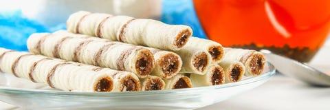 La gaufrette rayée roule, casse-croûte délicieux de chocolat sur la table en bois blanche photos stock