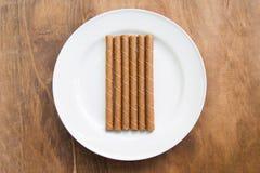 La gaufrette roule avec du chocolat dans le plat blanc sur la table en bois photographie stock