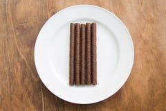 La gaufrette roule avec du chocolat dans le plat blanc sur la table en bois photos stock