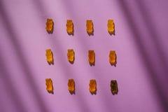 La gelée de sucrerie concerne le fond violet avec des ombres Surr?alisme unique bonbons Marmelade images stock