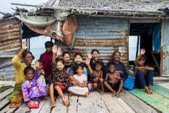 La generación tres de tribu de Bajau se sienta fuera de las manos que agitan fuera de su choza de madera Fotografía de archivo libre de regalías