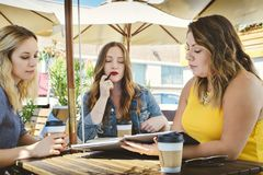 La generazione di giovani imprenditori millenari e femminili si incontra ad una caffetteria immagine stock