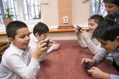 La generazione mobile scherza facendo uso dei loro dispositivi mobili per entertainm Immagine Stock