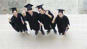 La gente è felice negli abiti di graduazione e nel supporto del cappuccio nella linea Immagine Stock Libera da Diritti