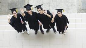 La gente è felice negli abiti di graduazione e nel supporto del cappuccio nella linea Fotografia Stock Libera da Diritti