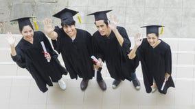La gente è felice negli abiti di graduazione e nel supporto del cappuccio nella linea Fotografie Stock