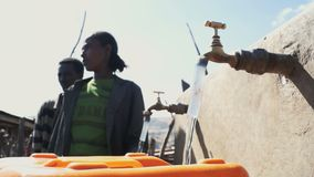 La gente acerca al punto de agua en Etiopía metrajes