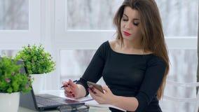 La gente acertada, muchacha de pelo largo utiliza el ordenador portátil y el móvil en el trabajo que se sienta en el escritorio e almacen de video