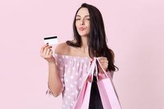 La gente, acquisto, vendite e concetto di finanze La donna graziosa con le labbra piegate, tiene i sacchetti della spesa e mostra immagini stock libere da diritti