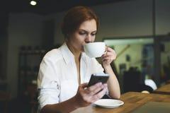 La gente ad Internet del lavoro mentre mangiando prima colazione in caffetteria Fotografia Stock Libera da Diritti
