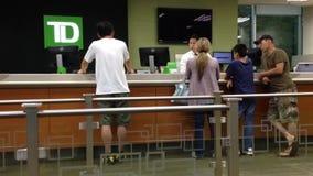 La gente ad un banco di servizio che parla con cassiere Immagini Stock Libere da Diritti