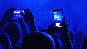 La gente ad un concerto rock è trasmettere per radio in tensione sulla rete sociale facendo uso di Smartphone stock footage