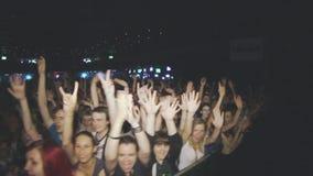 La gente agita las manos in camera en concierto de rock vivo en club nocturno griterío proyectores iluminación metrajes