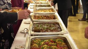 La gente agrupa la comida de abastecimiento del buffet interior en restaurante de lujo con la carne almacen de metraje de vídeo