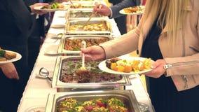 La gente agrupa la comida de abastecimiento del buffet interior en restaurante de lujo con la carne almacen de video