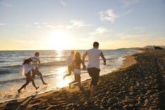 La gente agrupa el funcionamiento en la playa Foto de archivo libre de regalías