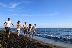 La gente agrupa el funcionamiento en la playa Foto de archivo