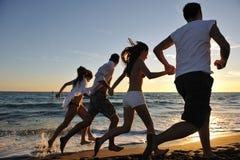 La gente agrupa el funcionamiento en la playa Fotografía de archivo libre de regalías