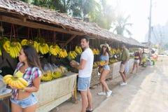 La gente agrupa plátanos y las piñas de compra en mercado tradicional de la calle, hombre joven y viajeros de la mujer Fotografía de archivo libre de regalías
