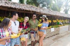 La gente agrupa plátanos y las piñas de compra en mercado tradicional de la calle, hombre joven y viajeros de la mujer Imagenes de archivo