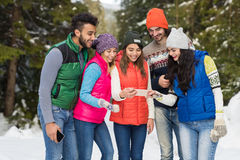 La gente agrupa usando el invierno al aire libre que camina de Forest Happy Smiling Young Friends de la nieve elegante del teléfo Imagen de archivo