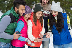 La gente agrupa usando el invierno al aire libre que camina de Forest Happy Smiling Young Friends de la nieve elegante del teléfo Imágenes de archivo libres de regalías