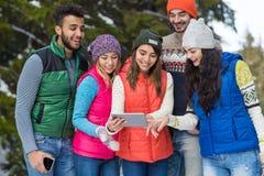 La gente agrupa usando el invierno al aire libre que camina de Forest Happy Smiling Young Friends de la nieve elegante del teléfo Foto de archivo libre de regalías