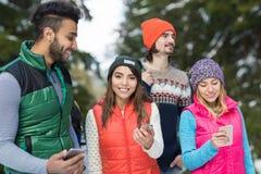 La gente agrupa usando el teléfono elegante que charla el invierno al aire libre que camina de Forest Happy Smiling Young Friends Fotos de archivo