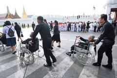 La gente aiuta l'anziano sulla sedia a rotelle alle devozioni per il funerale di re immagine stock