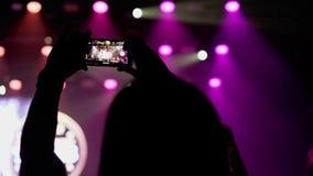 La gente al concerto in club, sparante sul telefono cellulare video d archivio