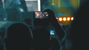 La gente al concerto rock di musica che prende le foto o che registra video con gli Smartphones stock footage