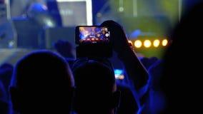 La gente al concerto rock di musica che prende le foto o che registra video con gli Smartphones archivi video