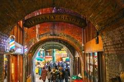 La gente al mercato della città che mangia l'alimento ha acquistato là come camminano tramite il tunnel del mattone a Londra Ingh Immagini Stock Libere da Diritti