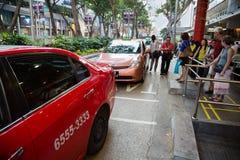 La gente al supporto di taxi alla strada del frutteto Fotografie Stock Libere da Diritti