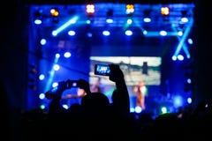 La gente al video o alla foto della fucilazione di concerto immagini stock