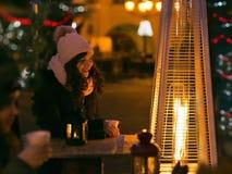 La gente all'aperto che sorseggia la perforazione di natale sulla notte di Natale Fotografia Stock