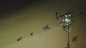La gente alla notte alla spiaggia di Copacabana Immagini Stock