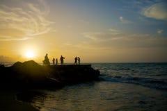 La gente alla spiaggia durante il tramonto 2 Fotografia Stock
